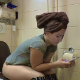 While drying her hair after a wash, a pretty, plump, Eastern-European girl sits down on a toilet to piss and take a shit. Occasional plops are heard as she continues to lean forward and push. About 7.5 minutes.
