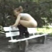 A woman poops while squatting on the edge of a park bench.