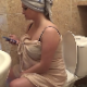 A plump girl who looks like she just got out of the shower sits on a toilet while farting repeatedly and pissing. We are not certain if the farts are genuine. Over 4 minutes.