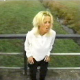 An attractive blonde girl positions her ass over the edge of some metal rails and takes a shit.