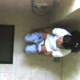 A hidden camera mounted on the ceiling captures a seemingly unsuspecting woman peeing on a toilet, then wiping. No audio.