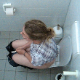 A daring cameraman video records an unsuspecting blonde girl using the adjacent toilet stall in a public restroom as she takes a shit and piss. 2 scenes. Loud plops in the first scene with good wiping. About 5.5 minutes.