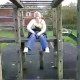 A girl pees while sitting up high on some playground equipment in a schoolyard in this very brief, low resolution video clip.