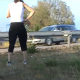 A woman takes a shit on the side of a busy road as cars speed by.