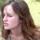 A low-quality video clip featuring an attractive brunette woman observed pooping in a natural setting outdoors.