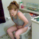A red-headed woman pees and has a wet-sounding bowel movement while sitting on a toilet. She plays around with her cell phone and does a lot of straining.