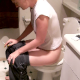 A red-headed woman has a hard-sounding bowel movement and then pees while sitting on a toilet. Several followup plops are heard. She smokes a cigarette and does a lot of straining. At the end of the 9.5-minute video, she wipes her ass.