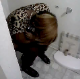 A black girl takes a shit in a ghetto house bathroom. There is no toilet paper, and the roll dispenser is broken. No pooping sounds that we could hear. Maybe you can hear it?