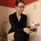 A brunette, naked Canadian girl wearing glasses takes a piss and a shit while sitting on a toilet and playing with her cell phone. Very subtle plop sounds can be heard. She wipes her ass when finished. Presented in 720P HD. Over 8 minutes.