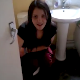 A brunette girl is video-recorded taking a shit while sitting on a toilet. There are no audible pooping sounds. The girl chases the videographer out of the bathroom, but the video continues through the bathroom window.