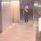 A homeless woman is caught peeing on the floor of an office building lobby by an employee. The whole event is captured on video by a security camera. No audio.