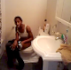 A black girl is video-recorded sitting on a toilet taking a crap. She yells at the videographer for recording her. There are no audible pooping sounds.
