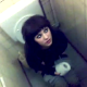 A brief video clip of a French girl, filmed by her friends, sitting on a toilet in a public restroom.