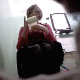 A floor mounted hidden camera records an older woman struggling to take a shit while sitting on a toilet. She did not wipe much, so she probably had little success going.