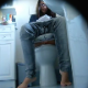 A hidden camera records a brunette girl wearing glasses as she wipes a stain from her panties and appears constipated while sitting on a toilet. Audio does not capture any noticeable poop sounds, but she wipes repeatedly. About 5.5 minutes.