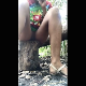 A dark-skinned woman takes a large, soft shit while smoking and sitting on tree stump. Vertical format video. About 1.5 minutes.