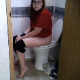 A brunette girl with glasses records herself taking a shit while sitting on a very tall toilet. Her feet barely touch the floor. She reads while going and then wipes her ass when finished. About 4.5 minutes.