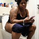 A big, black, British woman texts on her phone while sitting on a toilet. Plops and pissing is heard. She wipes her ass and shows us the dirty TP. Presented in 720P HD. About 4 minutes.