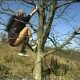 A European woman climbs a tree and takes a shit while hanging in the tree. Over 5 minutes.