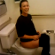 A pretty girl is video-recorded shitting while sitting on a toilet in a public restroom by her pretty friend. Pooping sounds are subtle, but completely audible. The girls react immediately to the bad smell. See video 3396 to watch the other girl pooping!