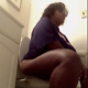 A big black woman takes a shit while sitting on a toilet. She is seen spraying deodorant into the air, reacting to her own smell, then wiping her ass. No poop is seen. About 7.5 minutes.