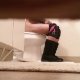 A voyeur cameraman records an unsuspecting girl taking a piss while sitting on a toilet from the view underneath a door. Presented in vertical HD format. About a minute.