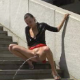 A brief video clip of women pissing in outdoor, urban settings in two scenes. About a minute.