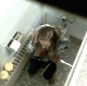 A girl is recorded pissing and shitting in a public restroom by some guy looking down from the ceiling. Pooping sounds are audible over the background noise. Presented in 720P HD video.