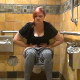 A plump girl takes a shit and a piss while sitting on a toilet in a public restroom. Some sporadic, soft, subtle plops can be heard while she grunts and pushes. About 5 minutes.